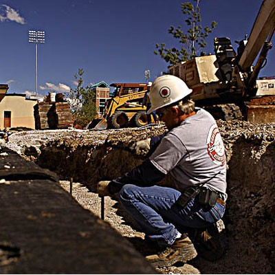Worker in trench building construction