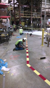 Installing safety tape on pedestrian walkway in warehouse