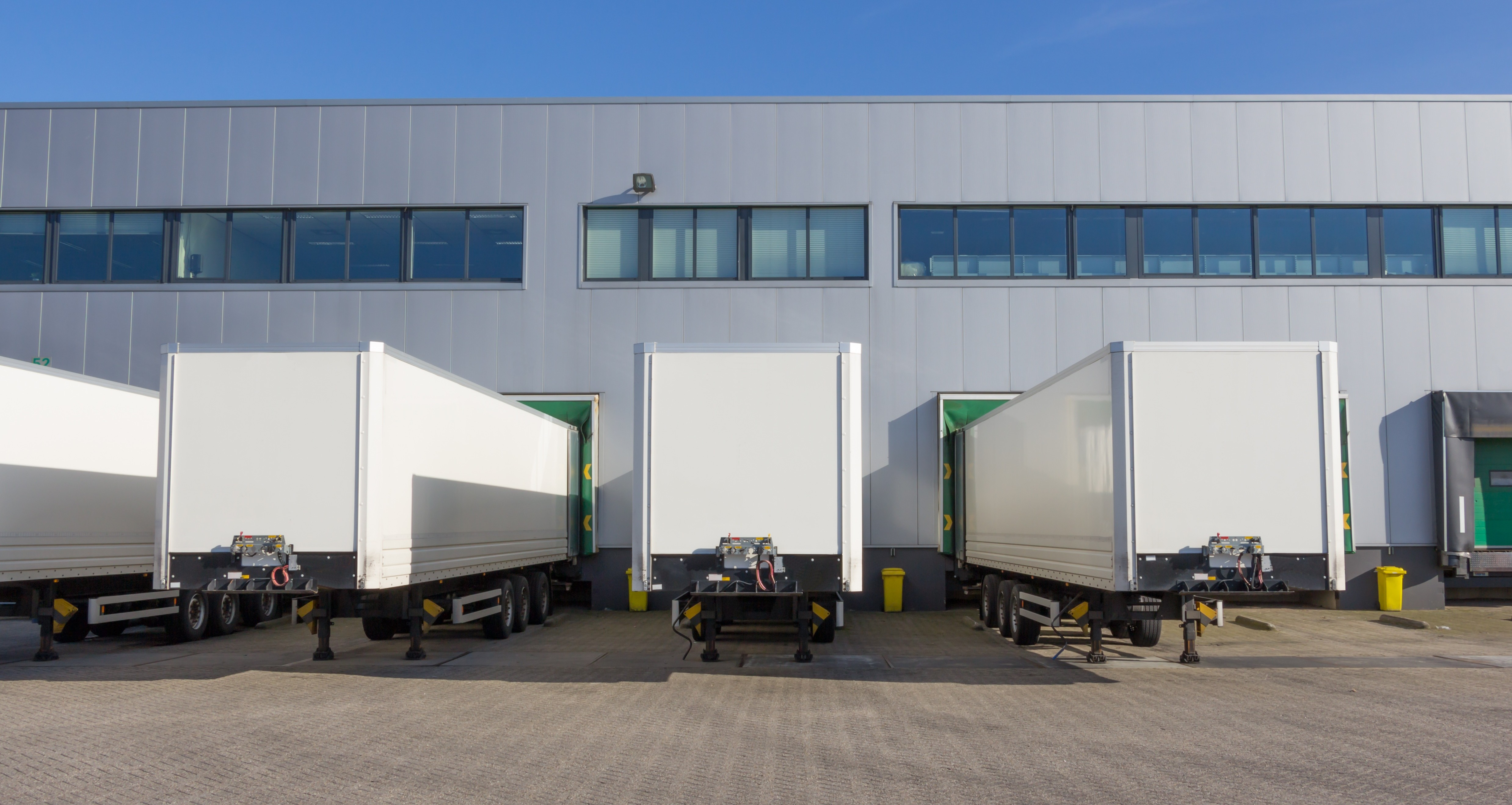 Trailers at docking stations of a distribution centre waiting to