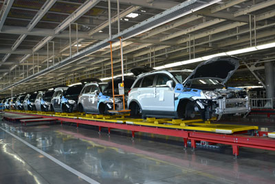 New cars move through a factory on a conveyor belt.