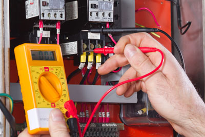 An electrician measures the power at an industrial electrical panel.
