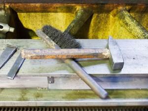 hammer and metal brush on machine frame