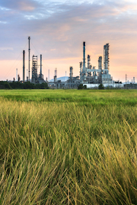An oil refinery with a green field in the foreground