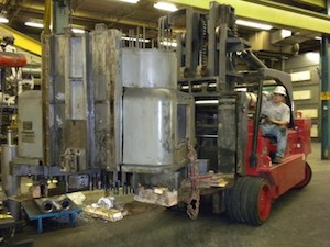 A forklift driver moving a piece of large manufacturing equipment