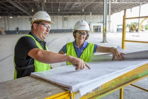 Two Storee project managers reviewing building construction plans